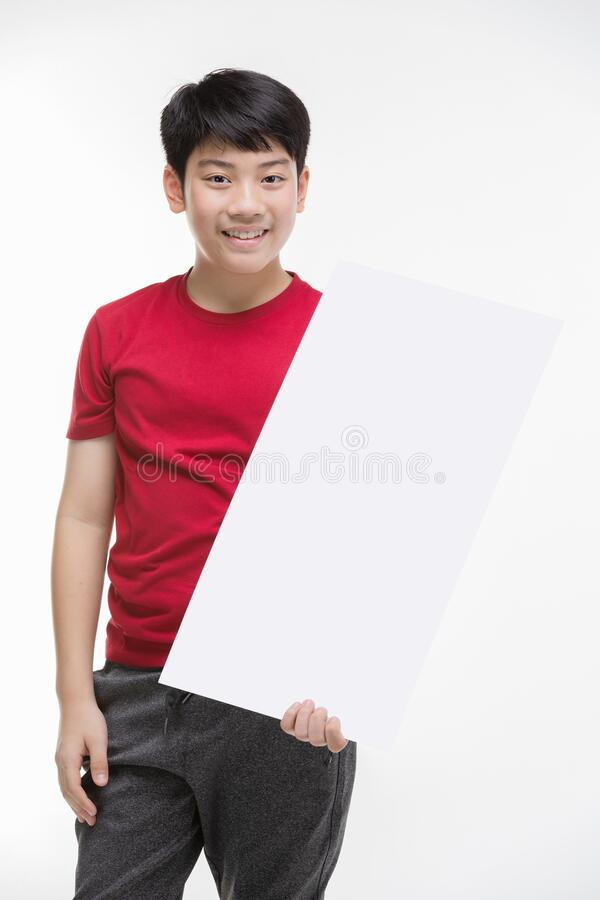 Boy holds blank sign. Teen boy holds empty billboard royalty free stock image