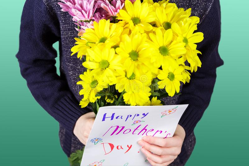 Boy holds a bouquet of yellow and pink chrysanthemums and handmade greeting card Happy Mother`s day in his hands. Flowers and gift royalty free stock photography
