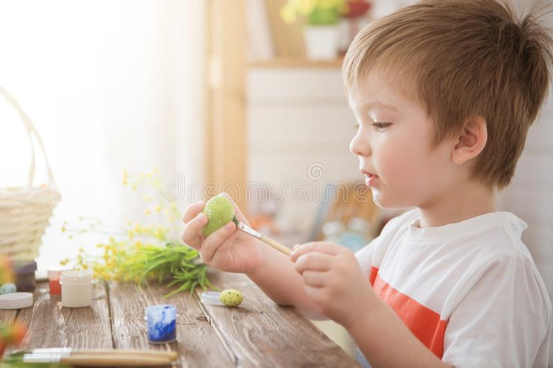 Boy holds an egg and painting with brush. Preparing for celebration of Easter. Little boy painting and decorating Easter eggs royalty free stock photos