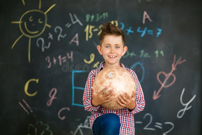 A boy holds a globe in front of a school board stock photography