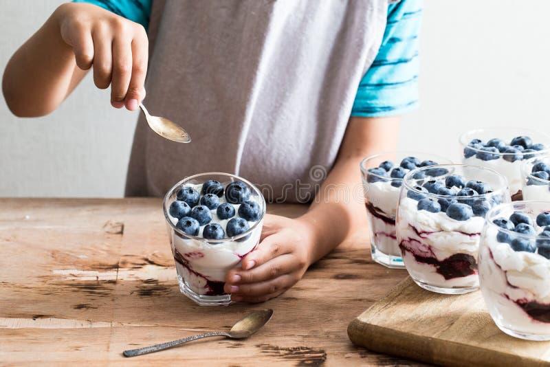 Boy holds homemade dessert with greek yogurt or cream, blueberry jam and fresh blueberries royalty free stock photo