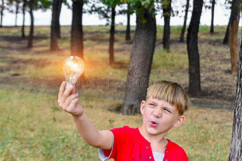 The boy holds an incandescent light bulb, which burns in his hand and looks at her with surprise and admiration.  stock photos