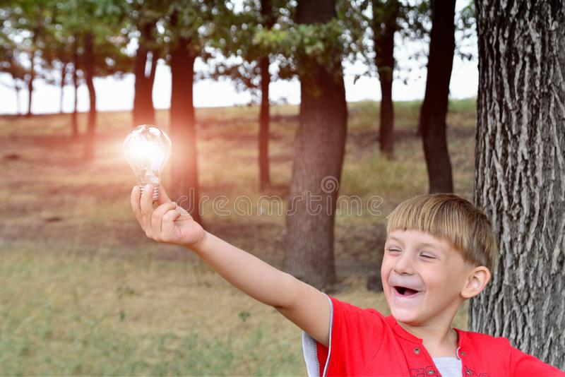The boy holds an incandescent light bulb, which burns in his hand and looks at her with surprise and admiration.  royalty free stock image