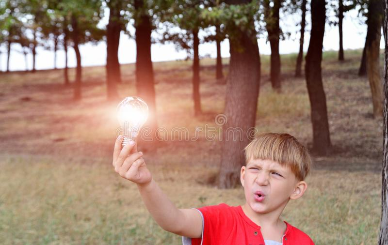 The boy holds an incandescent light bulb, which burns in his hand and looks at her with surprise and admiration.  royalty free stock images