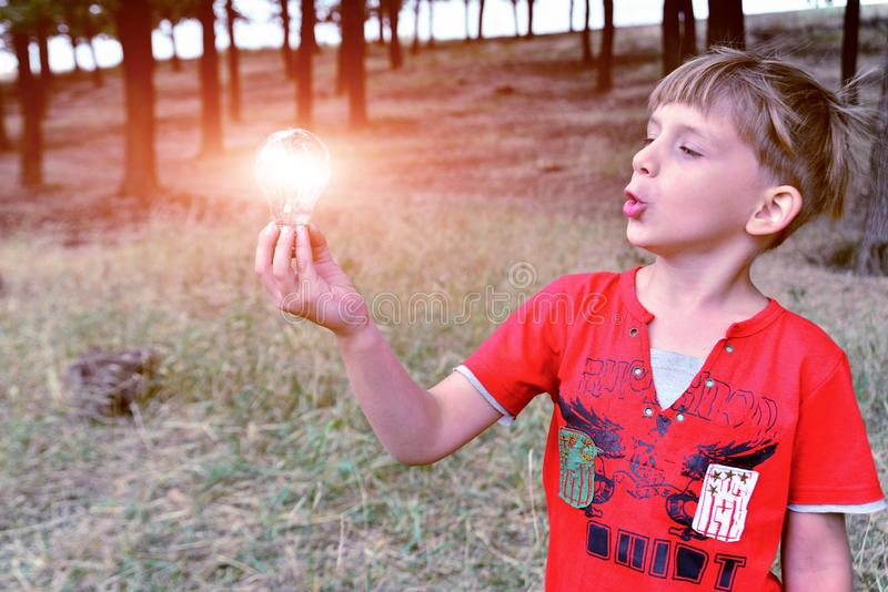 The boy holds an incandescent light bulb, which burns in his hand and looks at her with surprise and admiration.  royalty free stock photo