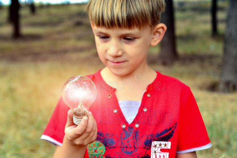 The boy holds an incandescent light bulb, which burns in his hand and looks at her with surprise and admiration.  stock images