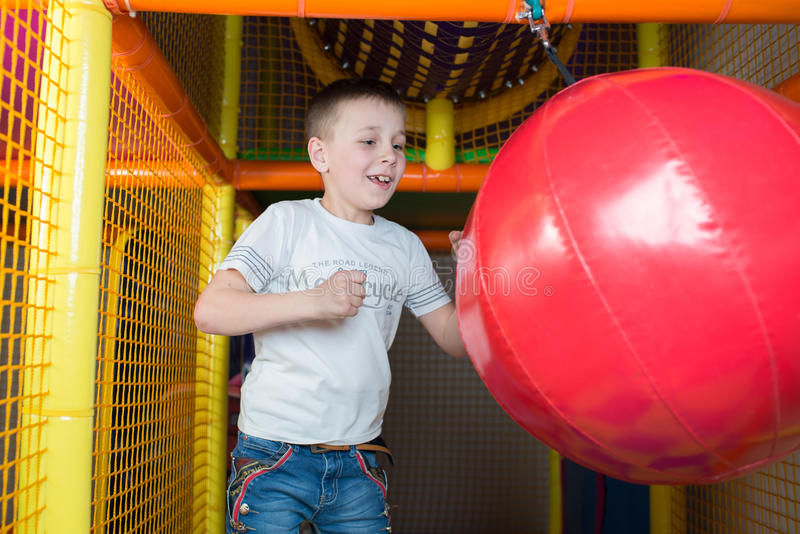 Boy holds a punching bag. In the children's playroom stock photo