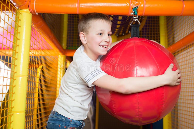 Boy holds a punching bag. In the children's playroom stock photos