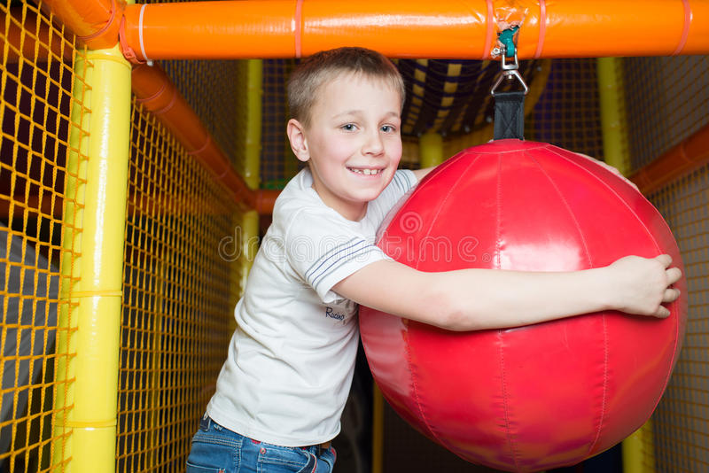 Boy holds a punching bag. In the children's playroom royalty free stock photos