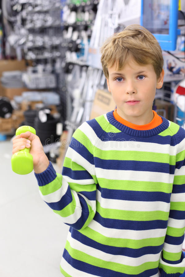 Boy holds small light green dumbbell. Boy in striped sweater holds small light green dumbbell in sports shop royalty free stock images