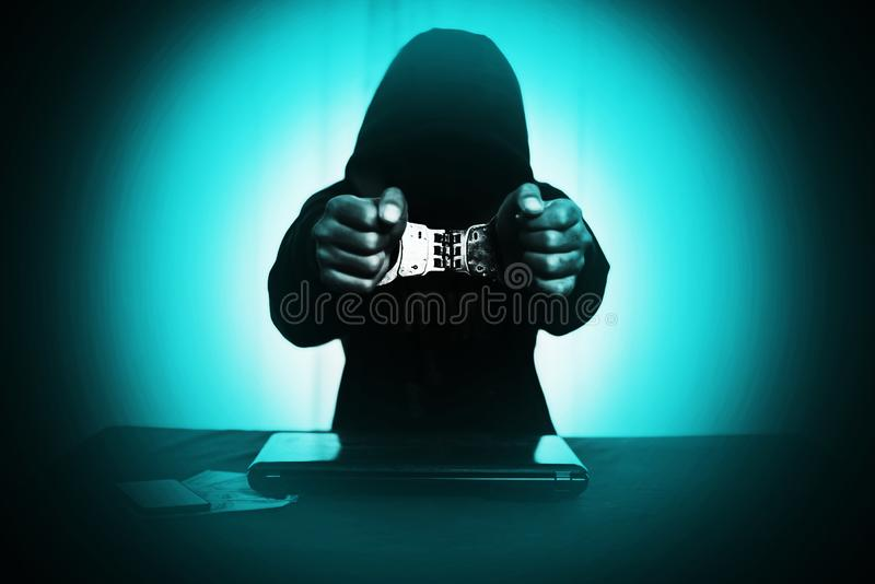 Boy in hood with handcuff at desk with laptop and money royalty free stock photography
