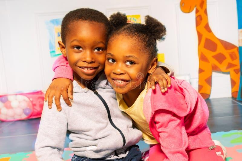 Boy hug girl African appearance in kindergarten stock image