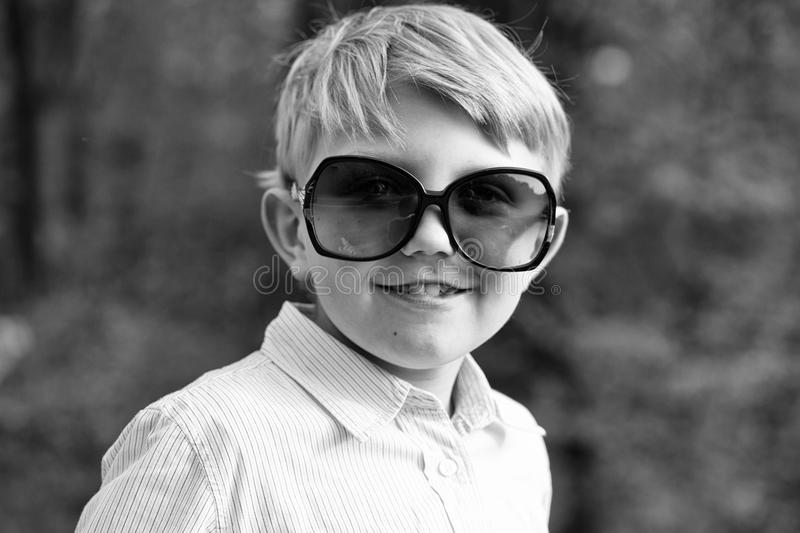 Boy in huge sunglasses. Cute baby boy in sunglasses stock photo