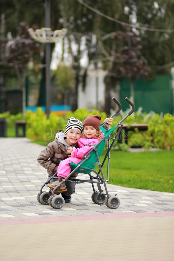 Boy hugging baby girl sitting in a stroller. Brother and sister on a stroll in the park, lovely autumn day. Looking at the camera. stock photos