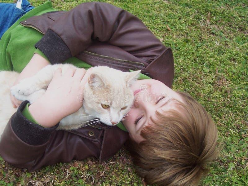 Boy hugging cat in field stock image