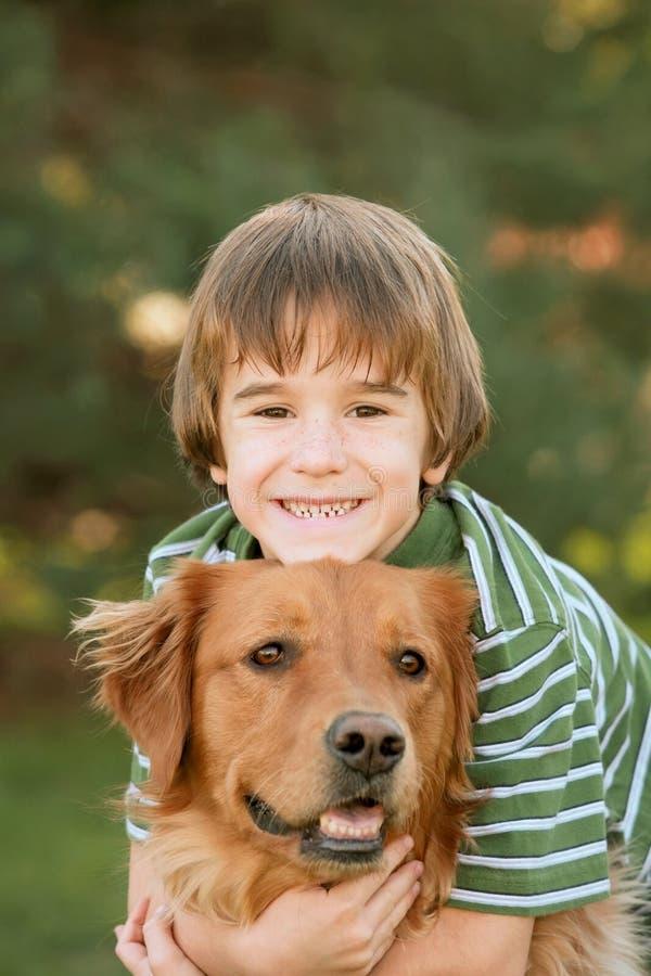 Boy Hugging Golden Retriever royalty free stock photos