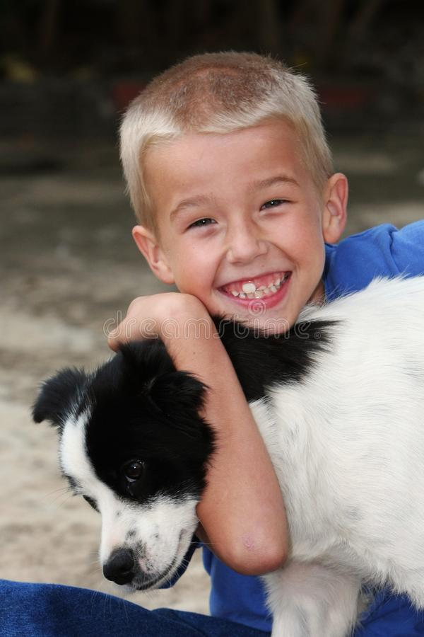 Boy Hugging His Dog stock images