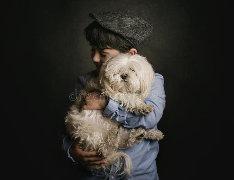 Boy hugging his dog. On black background royalty free stock photo