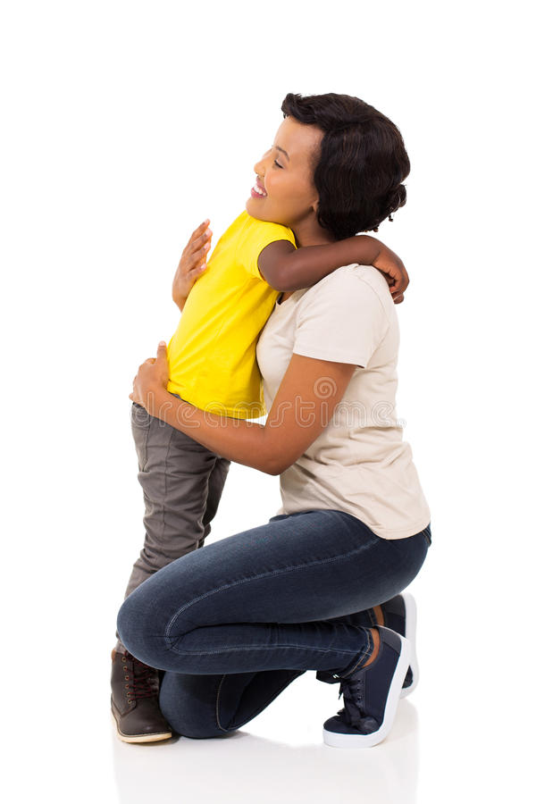 Boy hugging mother. Little afro american boy hugging his pretty mother on white background royalty free stock image