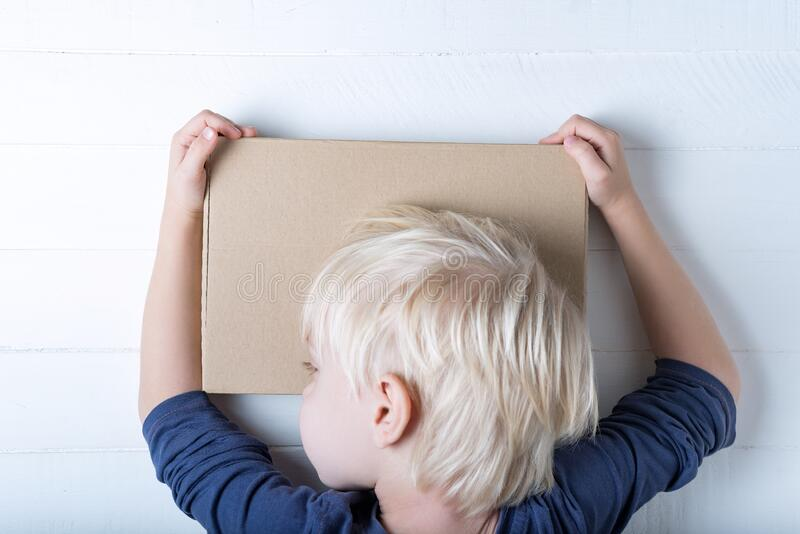 Boy hugging a parcel. Cute child holding a box. White background, top view royalty free stock images