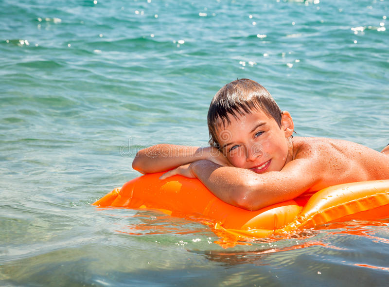 Boy on a inflatable mattress stock photography