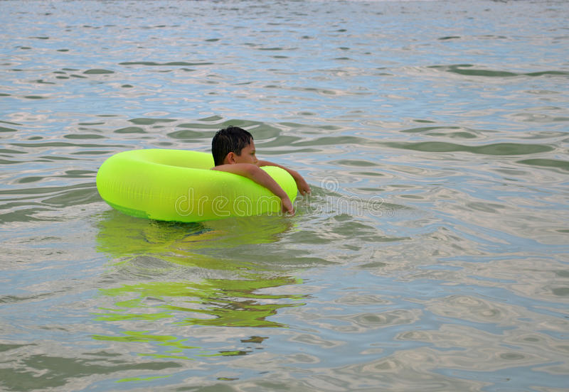 Boy in inflatable water toy stock photo