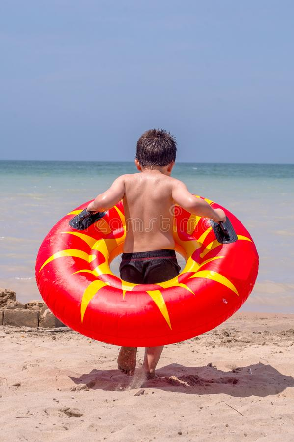 Boy with an inner tube heads to the water royalty free stock photos