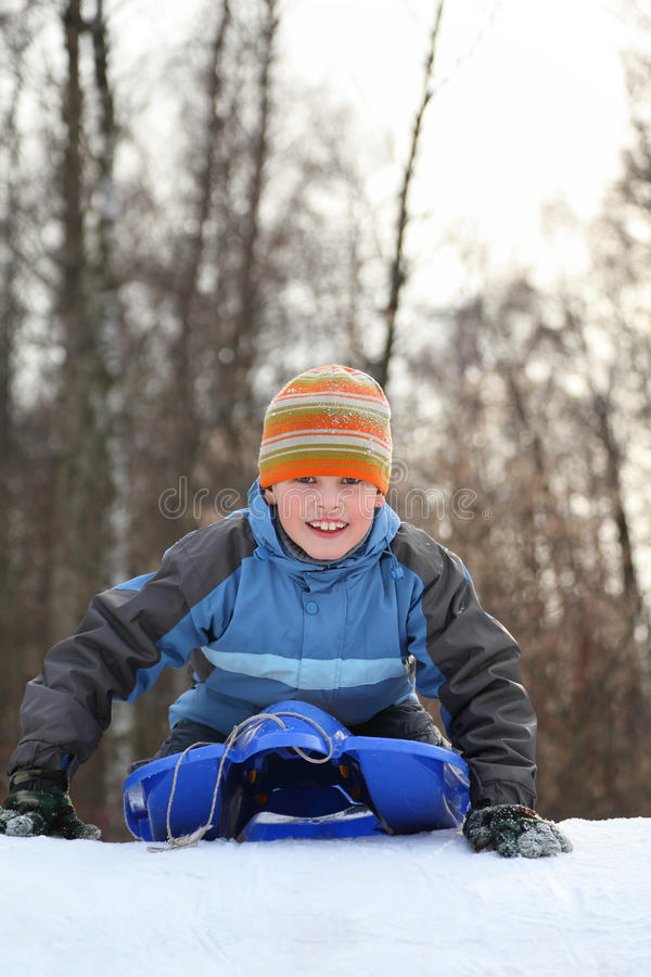 Boy intend drive from hill in winter on sledges stock photos