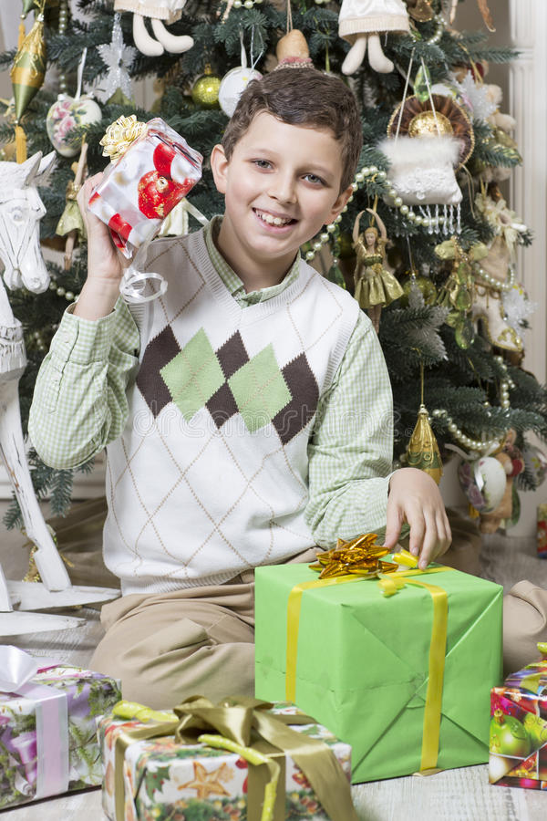 Download Boy Is Intrigued With Christmas Gifts Stock Photo - Image of ribbons, horse: 35237484