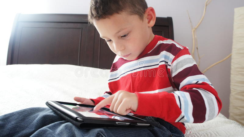 Boy with iPad. A boy siting on the bed playing on iPad