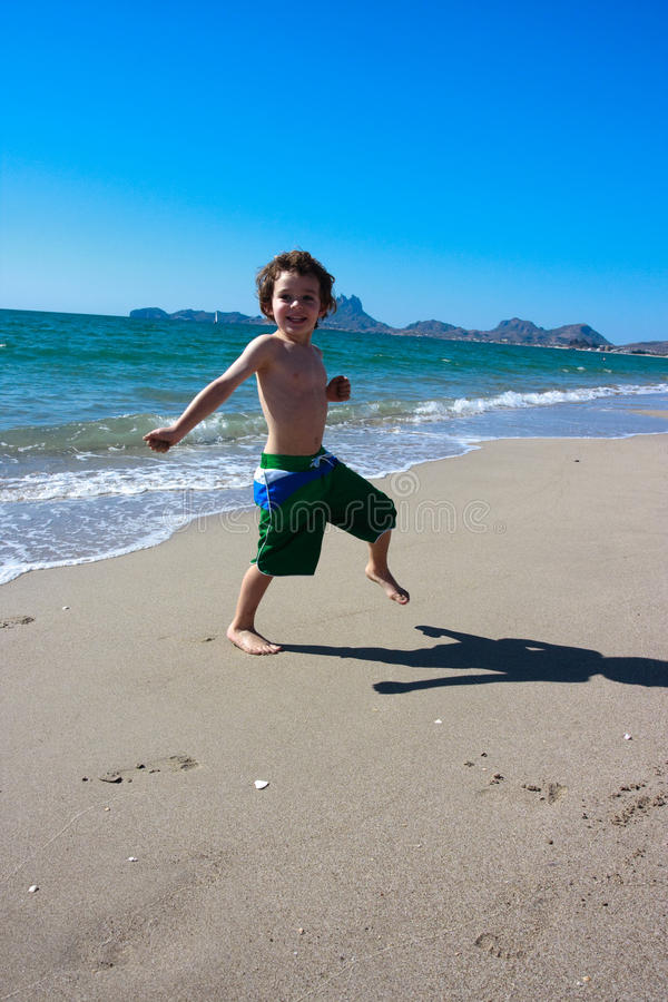 Boy jumping around on the beach stock photography