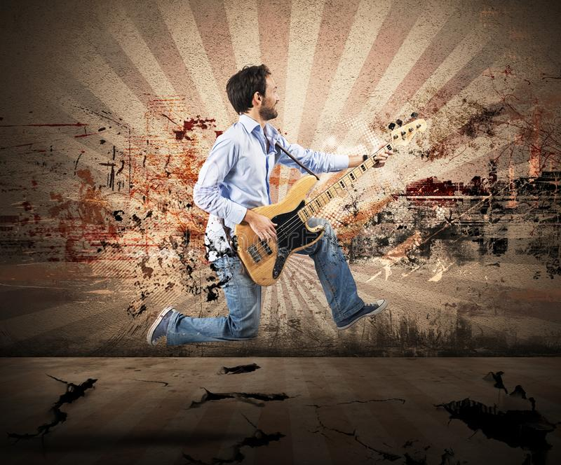 Boy jumping with bass guitar stock photography