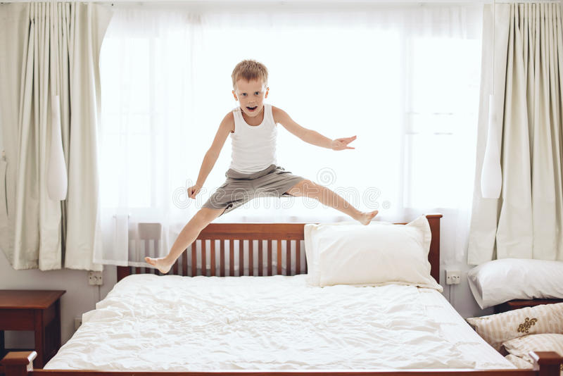 Boy jumping on the bed stock photo