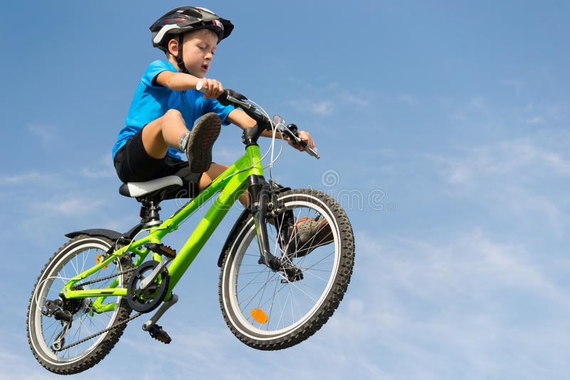 Boy jumping on bike stock photography