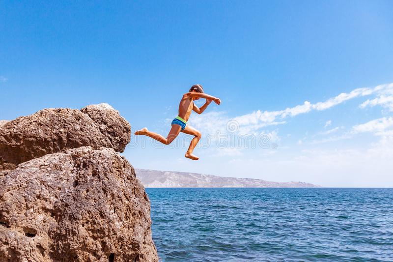 A boy is jumping from the cliff into the sea on a hot summer day. Holidays on the beach. The concept of active tourism. A boy is jumping from the cliff into the stock photography