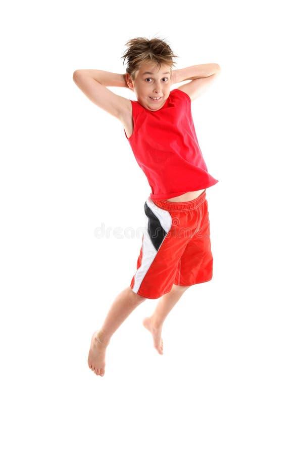 Boy jumping hands behind head royalty free stock photos