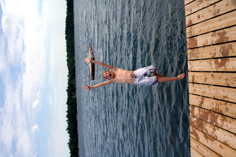 Boy jumping into lake. A boy jump off dock into lake at summer camp royalty free stock photos