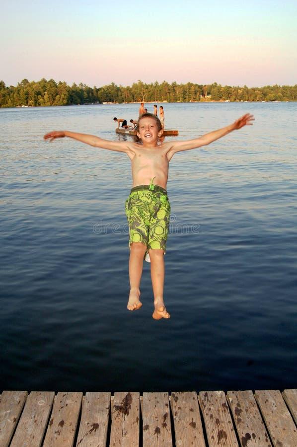 Boy jumping into lake royalty free stock photography