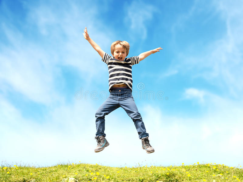 Boy jumping in meadow royalty free stock image