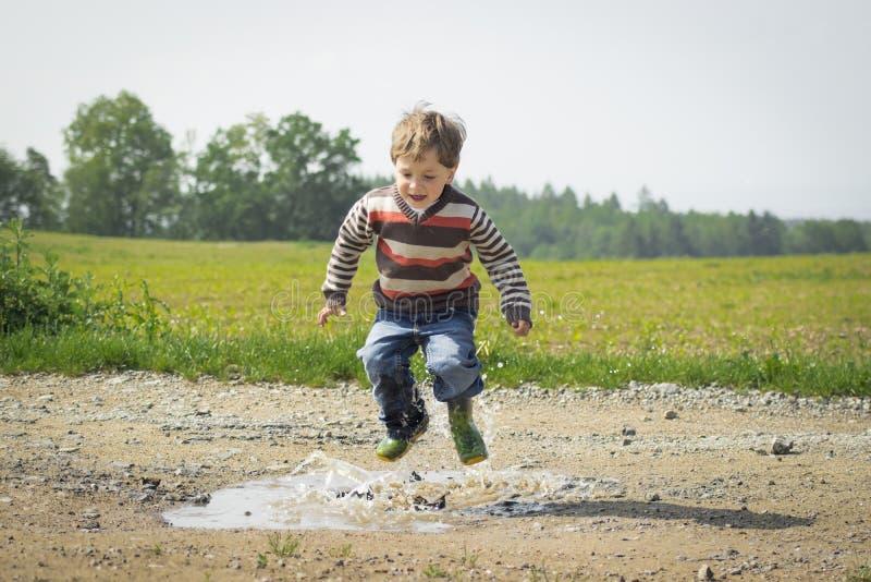 Boy Jumping Near Grass at Daytime stock photography