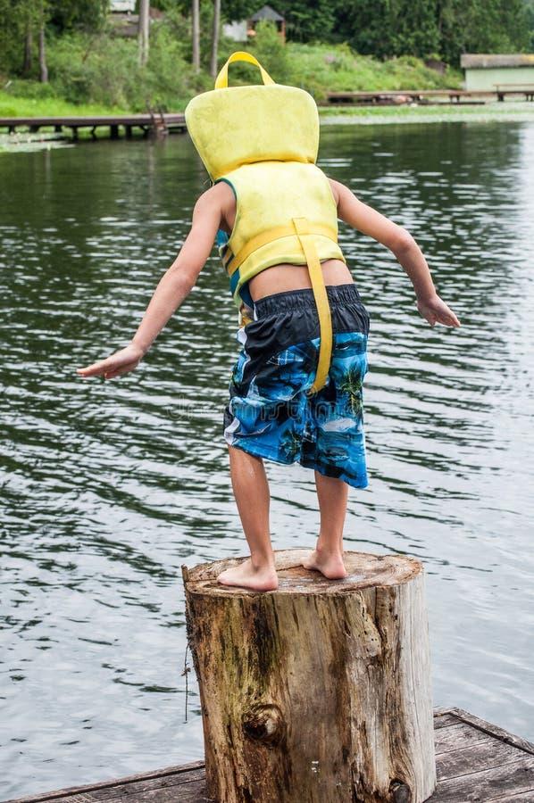 Boy jumping off dock royalty free stock photos