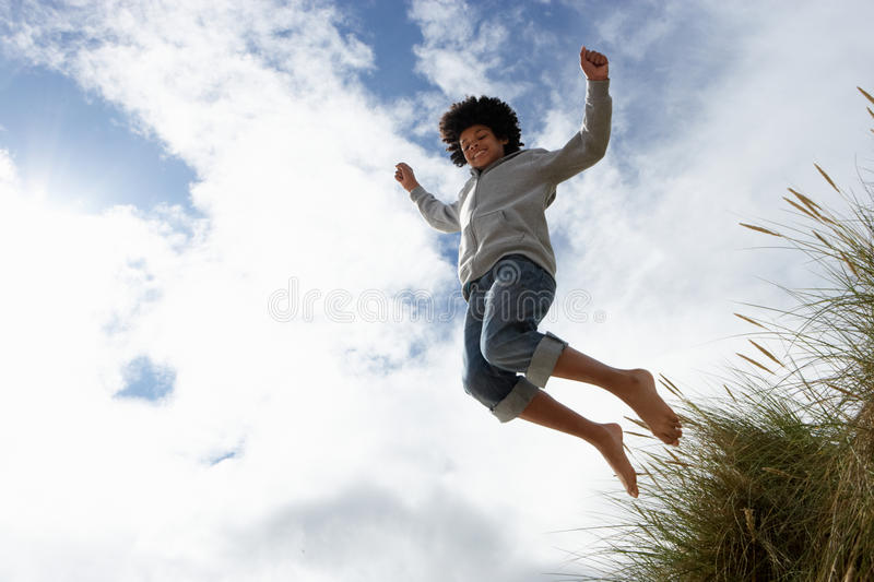 Boy jumping over dune