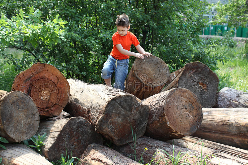 Boy Jumping Over Logs Stock Images