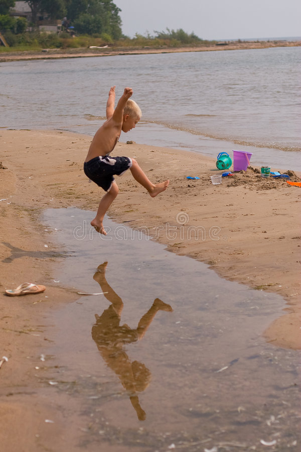 Boy jumping over puddle stock photos