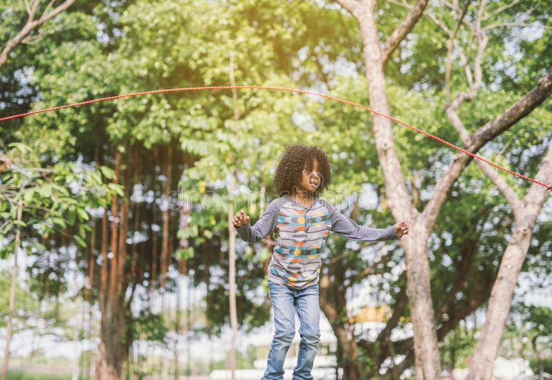 Boy jumping over the rope in the park on sunny summer day. royalty free stock photos