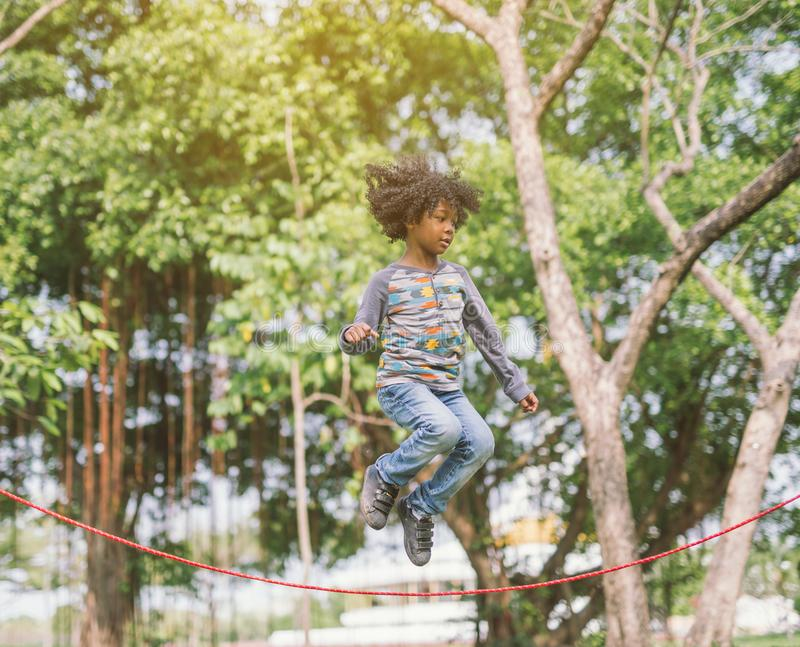 Boy jumping over the rope in the park on sunny summer day. stock photo
