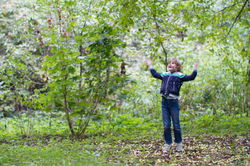 Boy jumping and playing with green apples royalty free stock photo