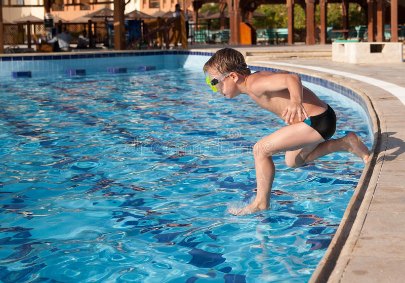 Boy Jumping Into The Pool Stock Image