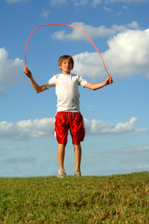 Boy jumping rope. A 12 year old boy jumping rope outdoors on a hill stock images