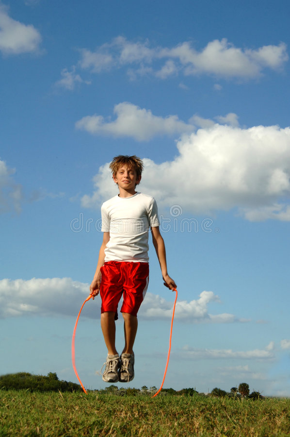 Boy jumping rope. A 12 year old boy jumping rope outdoors on a hill stock photos